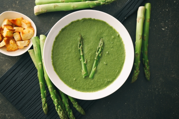 Tasty asparagus soup on table